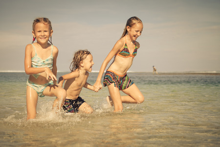 three happy kids playing on beach at the day time photo