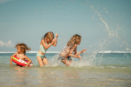 running water: Happy kids playing on the beach at the day time