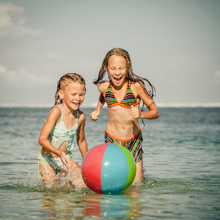 child ball: two sisters playing on the beach at the day time Stock Photo