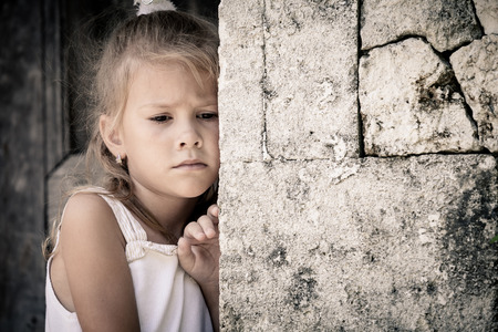 Retrato de niña triste que se coloca cerca de la pared de piedra en el tiempo del día