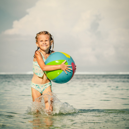 little girl running on the beach at the day time photo