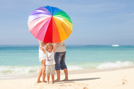 sun umbrella: Happy family standing at the beach in the day time