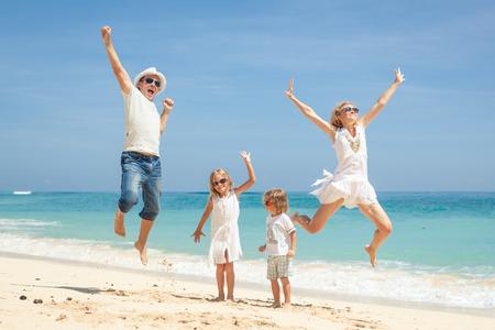 Familia feliz que salta en la playa en el momento del amanecer