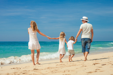 day time: Happy family walking at the beach at the day time  Concept of friendly family