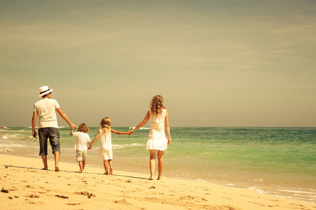 Happy family walking at the beach at the day time  Concept of friendly family