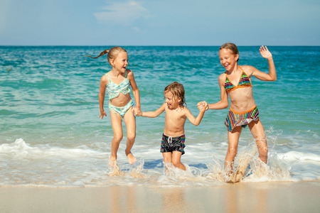 three persons: Happy kids playing on beach at the day time  Concept of friendly family