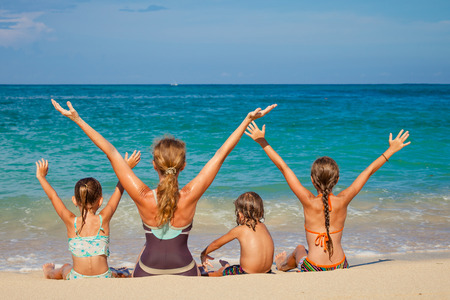 Happy family sitting on the beach at the day time Stock Photo