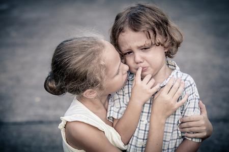 Portrait of sad teen girl and little boy photo