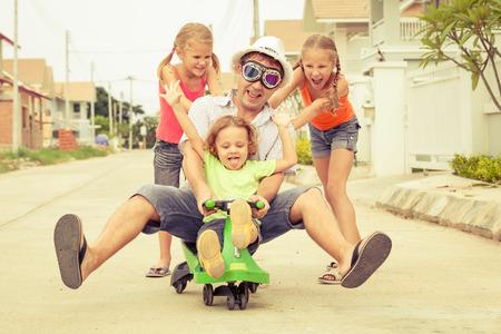 padre y los niños que juegan cerca de una casa en el tiempo del día
