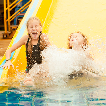 two little kids playing in the swimming pool photo