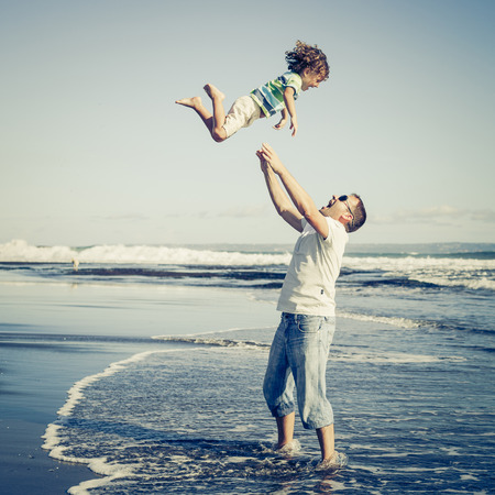 couple having fun: father and son playing on the beach at the day time
