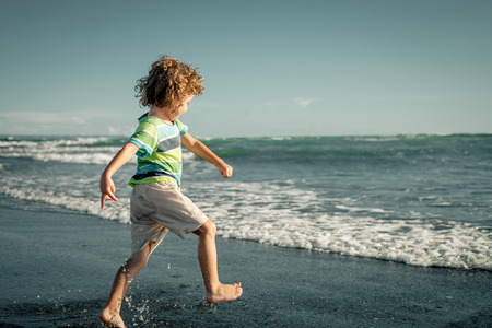 little boy running on the beach at the day time photo