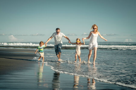 family time: Happy family playing on the beach at the day time. Concept of friendly family.