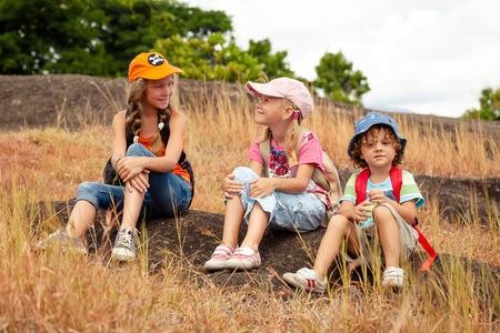 drie kleine kinderen met rugzak zitten op het voetpad in de bergen op de dag de tijd Stockfoto