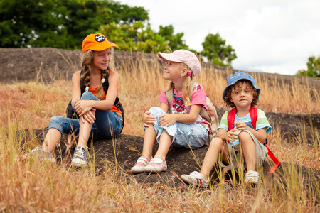 summer sport: three little kids with backpack sitting on the footpath in the mountains at the day time