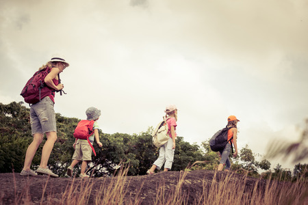 country boy: three little kids and mother in the mountains at the day time Stock Photo