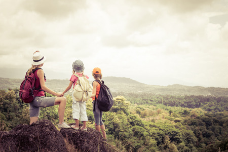 day time: two little kids and mother standing on the mountain at the day time
