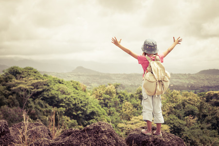 klein meisje met een rugzak staande op een bergtop op het moment van de dag