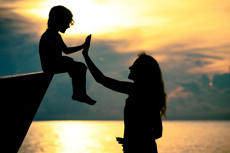 kids having fun: Silhouette of happy family who playing on the beach at the sunset time. Concept of friendly family. Stock Photo