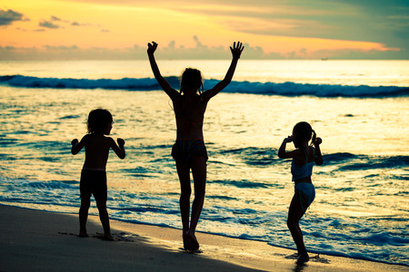 Happy children playing at the beach at the dawn time photo