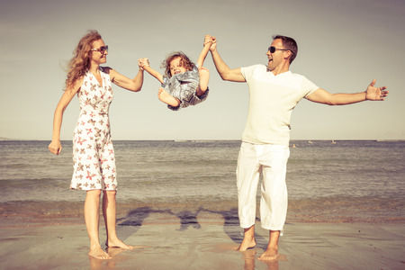 family time: Happy family walking at the beach at the day time. Concept of friendly family.