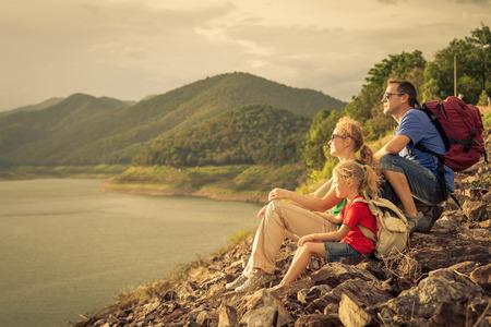 幸せな家族は湖の近く、一日の時間に座っています。フレンドリーな家族の概念。
