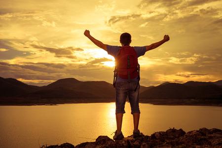 personas mirando: Hombre que est� a la orilla de un lago de monta�a y levanta sus brazos al cielo