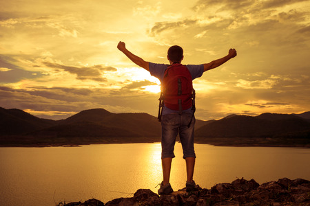 people: man standing on the shore of a mountain lake and raises his arms to the sky Stock Photo
