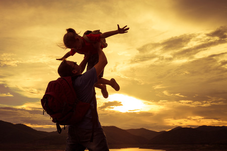 father and daughter playing on the coast of lake in the mountains of at the sunset time photo