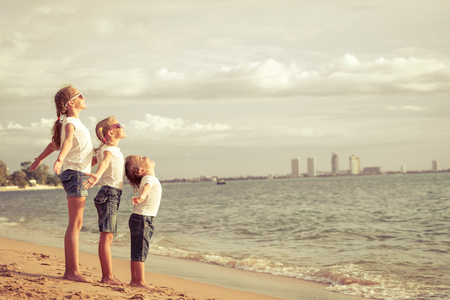 brothers and sisters: Three happy children standing on the beach at the day time