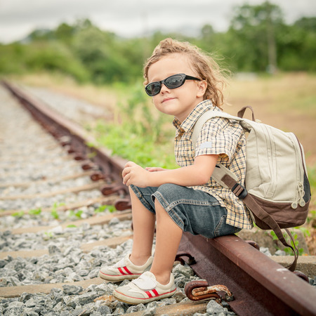 little boy with backpack sitting on the railway photo