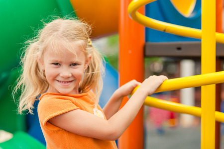 school playground: Happy little girl on the playground at the day time