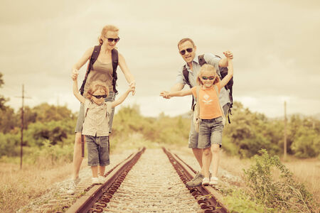 Happy family walking on the railway at the day time. Concept of friendly family. photo