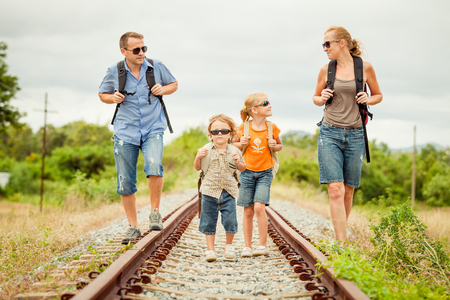 family time: Happy family walking on the railway at the day time. Concept of friendly family. Stock Photo