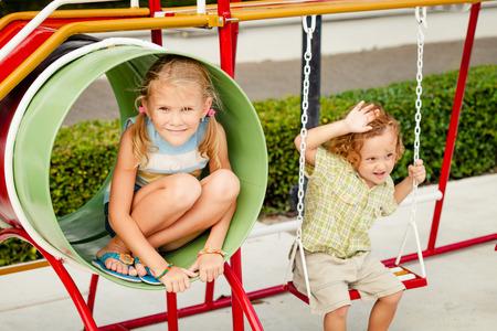 niños jugando en la escuela: Dos niños felices en el patio de recreo en el tiempo del día. Concepto hermano y hermana para siempre. Foto de archivo