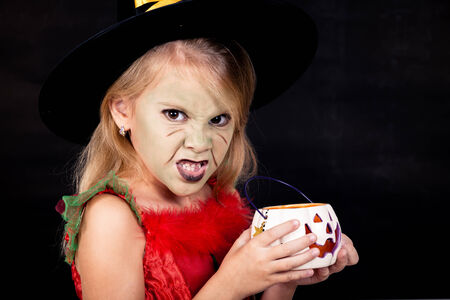 Portrait of little girl in costume witch on Halloween party photo