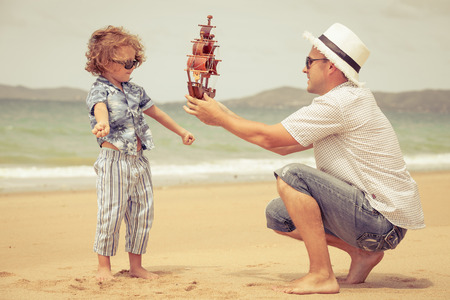 ship with gift: Father and son playing on the beach at the day time. Concept of friendly family.