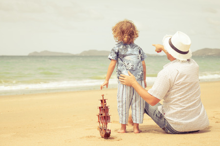Father and son playing on the beach at the day time. Concept of friendly family. photo