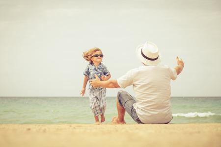 niño corriendo: Padre e hijo que juegan en la playa en el día. Concepto de familia. Foto de archivo
