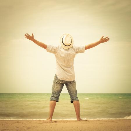하루 시간에 해변에 서서 손을 올리는 남자의 초상 스톡 콘텐츠