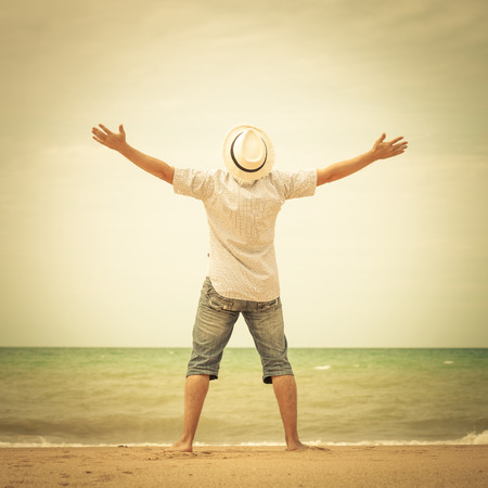 portrait of  man standing on the beach at the day time and raising hands Foto de archivo
