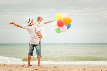 Father and daughter with balloons playing on the beach at the day time. Concept of friendly family. Stock Photo