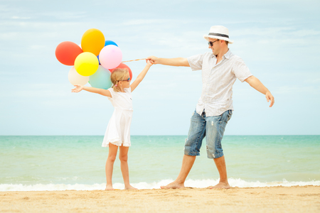 kids having fun: Father and daughter with balloons playing on the beach at the day time. Concept of friendly family. Stock Photo