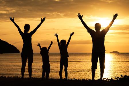 papa y mama: Silueta de la familia feliz que juega en la playa en el momento de la puesta del sol. Concepto de familia. Foto de archivo