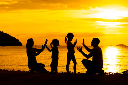 Silhouette of happy family who playing on the beach at the sunset time photo