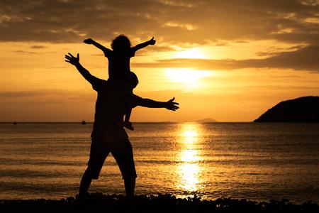 day: Padre e hijo que juegan en la playa de la puesta del sol.