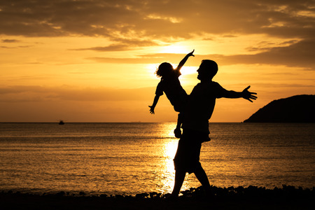 Father and son playing on the beach at the sunset time. photo