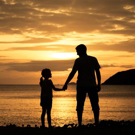 father and daughter: Padre e hija que se colocan en la playa en el momento de la puesta del sol. Foto de archivo