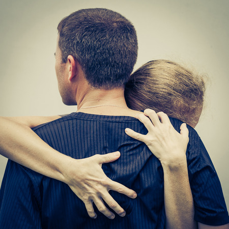 abusive man: Sad woman hugging her husband Stock Photo