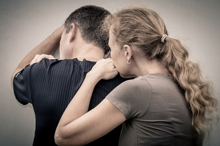 shoulder problem: Sad woman hugging her husband Stock Photo